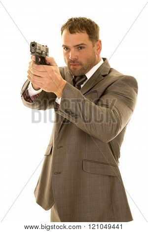 A man in his suit with a serious expression on his face pointing his gun.