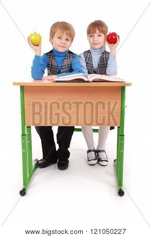 Boy And Girl Sit At A School Desk And Holding Apple