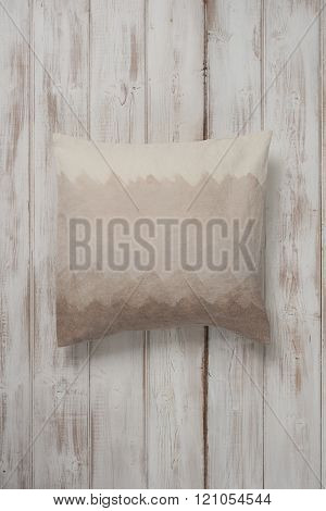 Square Gradient Brown Throw Pillow Laid Flat On Wooden Surface