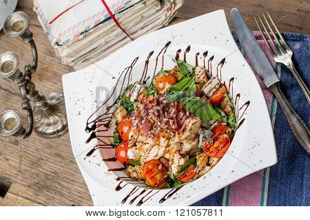 Tasty grilled chicken salad with rucola cherry tomatoes valerian basil seeds bread crumbs in a white plate an old wooden table