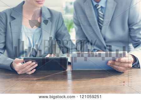 Business interface with graphs and data against business people discussing over tablet pcs