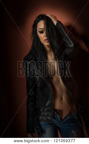 Attractive sexy brunette in black leather jacket and jeans posing provocatively indoor. Portrait of sensual woman with long dark hair without lingerie, studio shot. Attractive young female tempting