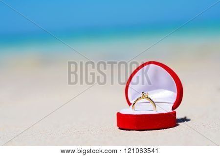 Golden Wedding ring on the sandy beach