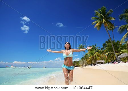 Carefree young woman playing in the clear water on exotic beach.