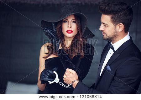 Sexy woman with hat and handcuffs holding lover man