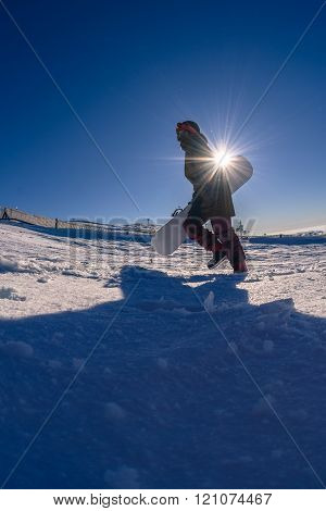 Snowboarder Walking Against Blue Sky