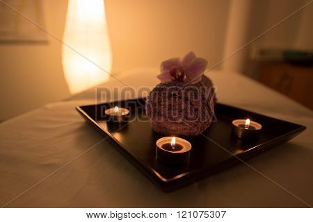 Beauty salon decoration in massage room, candles, towel and orchid.
