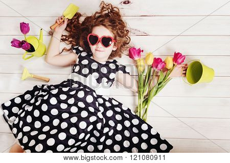 Curly girl with bouquet of tulips lying on white wooden floor. Spring background Birthday party Healthy lifestyle Valentine day concept.