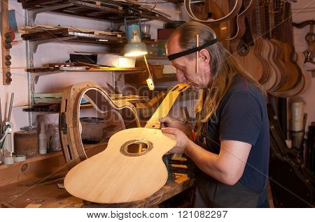 Russian luthier at his desk makes the acoustic guitar