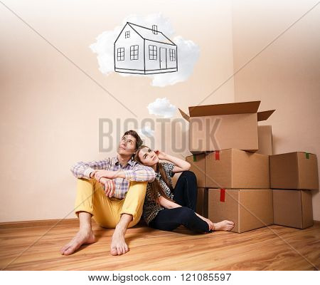 Young couple sitting on the floor and daydream