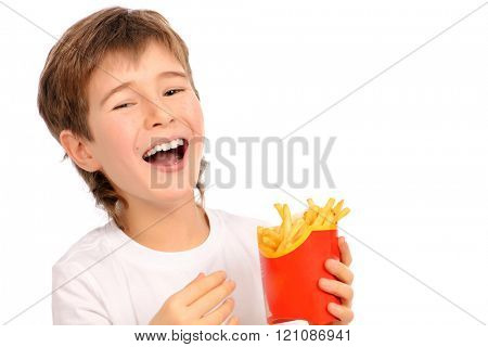 Happy nine year old boy eating french fries and laughing. Fast food. Concept of healthy and unhealthy food. Isolated over white.