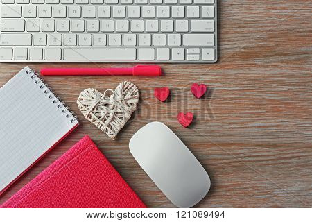 Computer peripherals with hearts, pen and notebooks on wooden table