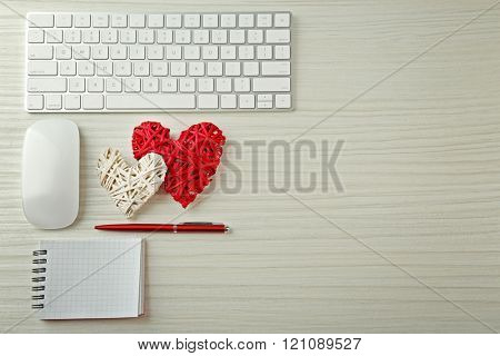 Computer peripherals with wicker hearts, pen and notebook on light wooden table