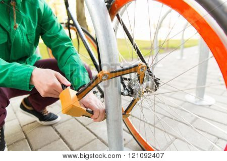 people, people, security, safety and transport - close up of man fastening bicycle lock on street parking
