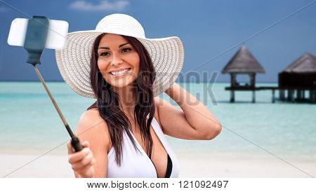 lifestyle, leisure, summer, technology and people concept - smiling young woman or teenage girl in sun hat taking picture with smartphone on selfie stick over bungalow on beach background