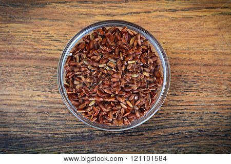Red Rice on Wooden Background