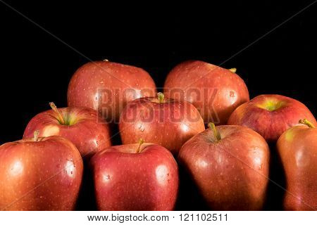 Juicy apples with water droplets on black background.