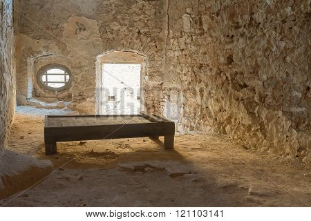 Nafplio, Greece, 28 December 2015. Old prison cell at Palamidi castle in Greece with a wooden bed.