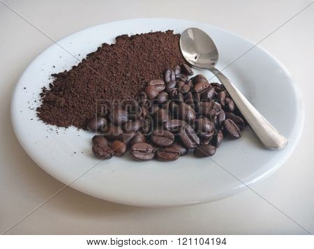 Milled Coffee On A White Plate With Spoon