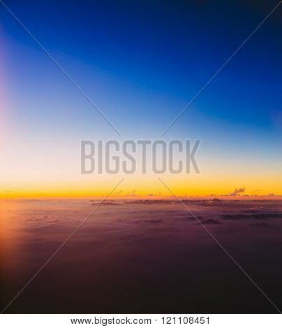 Beautiful colorful sunset over mountains from height of airplane