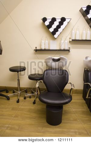 a black leather chair in a hair salon poster