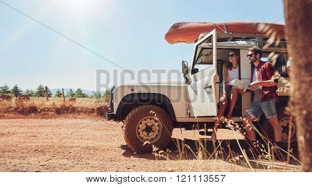 Young couple with car on road trip reading map for directions. Young man and woman taking break from the road trip. poster
