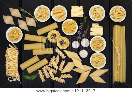 Dried italian pasta food selection forming an abstract background over dark wood.