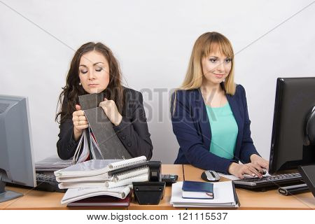 Female Colleagues In The Office, One Asleep On A Folder, The Other Happy Working On A Computer