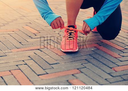 young woman runner tying shoelace on road