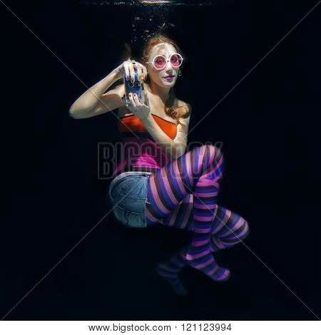 red hair funny girl in colorful clothes and pink sunglasses with tatto on the dark background swimmi