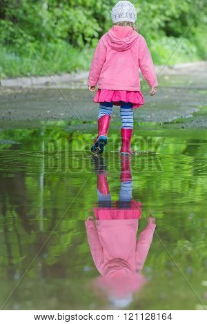 Back view full length portrait of little girl wearing red gumboots walking in big spring puddle