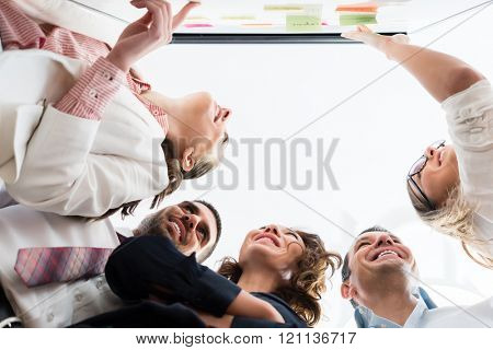 Group of business people in office at creative brainstorming at board, low angle