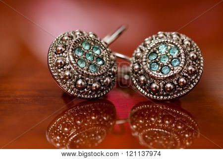 Silver Earrings Sitting On Shiny Surface