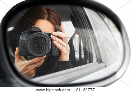 Photographer using her professional camera. Photographer girl  in the car window. Mobile reporter with the DSLR camera. Photojournalist at work. 