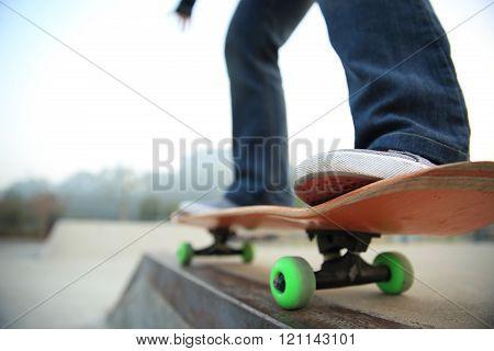 young skateboarder legs skateboarding at skate park