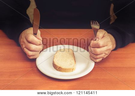 Old Man's Hands Holding Knife And Fork With One Slice Of Bread In Middle