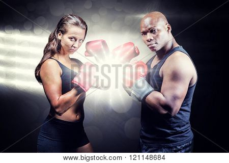 Portrait of male and female athletes with fighting stance against spotlight Portrait of male and female athletes with fighting stance against black background