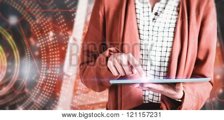 Businesswoman using a tablet against futuristic shiny spiral on black background