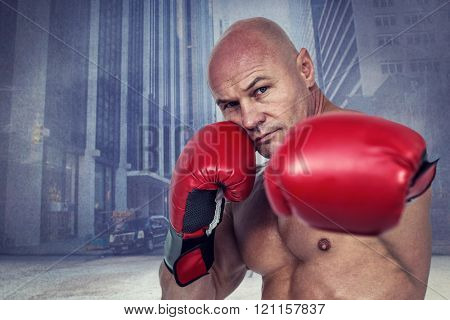 Portrait of boxer with fighting stance against urban projection on wall