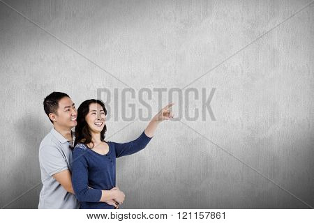 Happy couple with woman pointing up against white and grey background