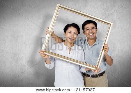 Older asian couple with frame against white and grey background