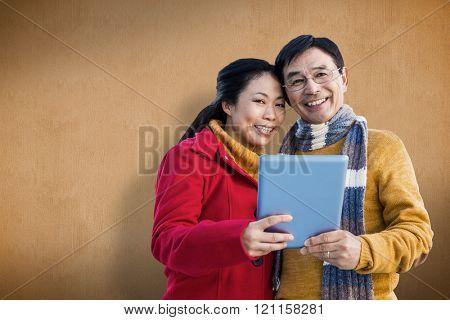 Asian couple on balcony using tablet against orange background