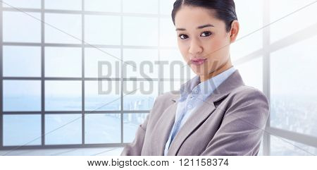 Portrait of a gorgeous businesswoman posing with the arms crossed against room with large window showing city