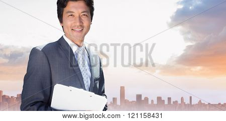 Confident estate agent standing at front door with clipboard against sandy path leading to large urban city