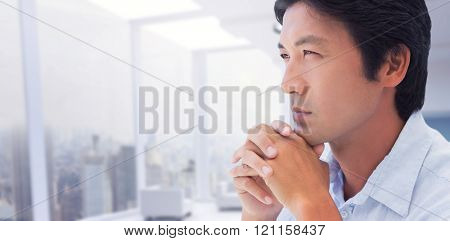 Thinking man with hands together against modern room overlooking city