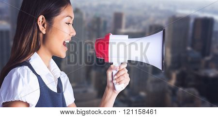 Businesswoman shooting through a megaphone against view of cityscape