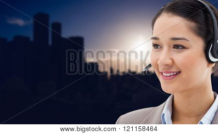 Happy operator posing with a headset against picture of city by sunrise