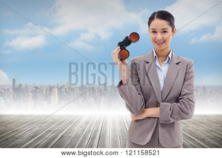 Portrait of a businesswoman holding binoculars against cityscape on the horizon