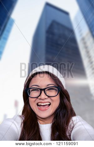 Asian woman smiling at the camera against skyscraper in city