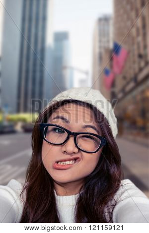 Asian woman making faces against new york street